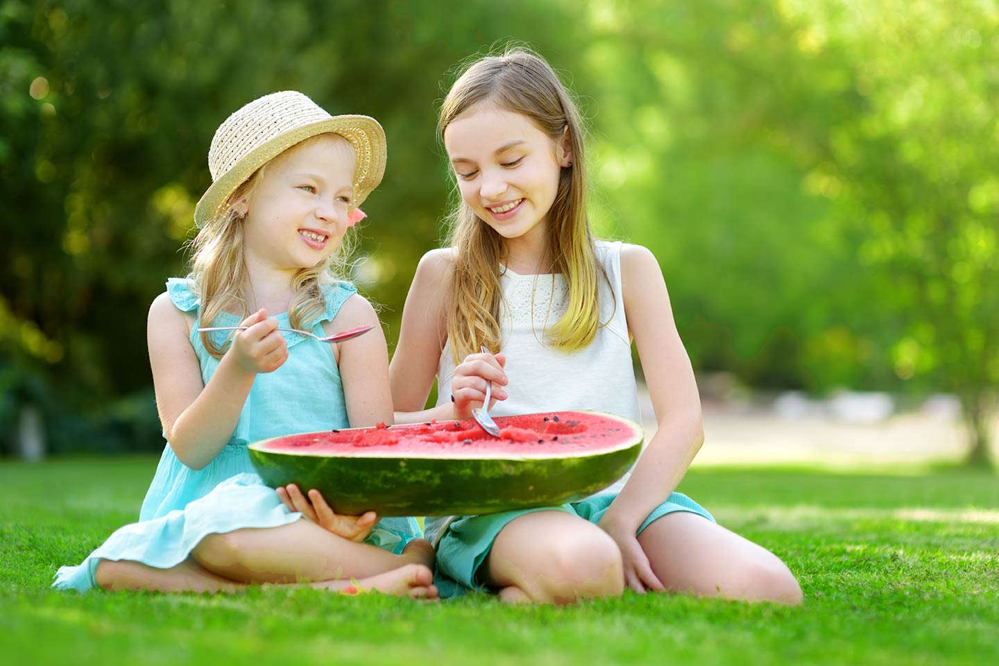 2 girls eating a watermelon on the lawn