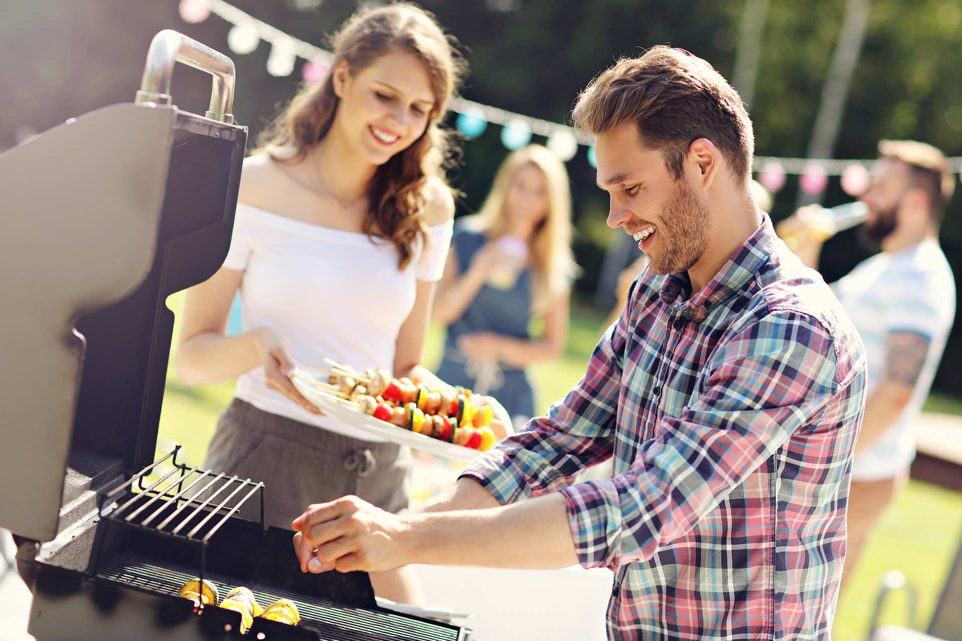 a man grilling food for a backyard party