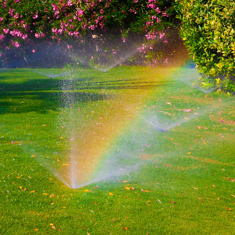 sprinkler system on lawn creating a rainbow in the mist
